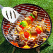Tasty beef kebabs grilling over glowing coals