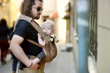 Young father and baby girl in a baby carrier
