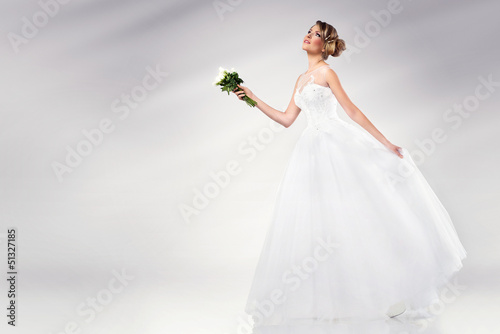 beautiful young bride wearing wedding dress holding flowers
