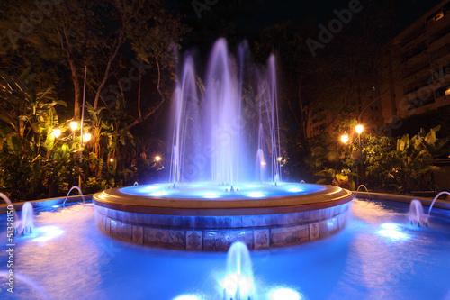 Leinwanddruck Bild Blue illuminated fountain in Marbella, Spain