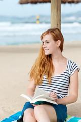 entspannte frau mit buch am strand