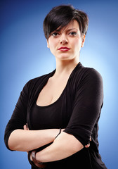 Brunette with crossed arms on blue background