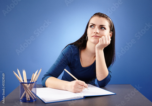 Young pensive student sitting at her desk