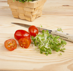 Watercress, tomatoes, knife on wooden table
