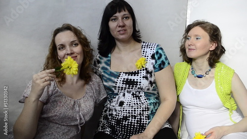 Three pregnant woman with yellow flowers in the studio