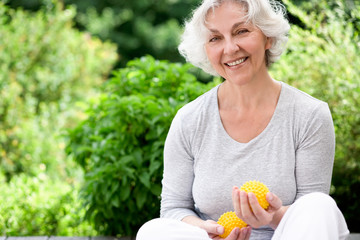 Aktive Seniorin. Gymnastik im sommerlichen Garten