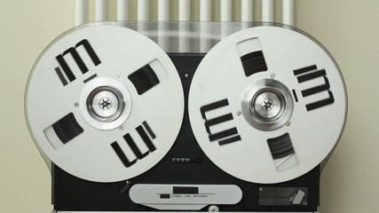 Reel to reel tape playing on a tape machine, close up
