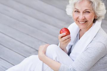 sportliche, grauhaarige Frau mit rotem Apfel
