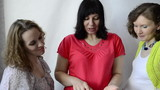 Three pregnant women view photos