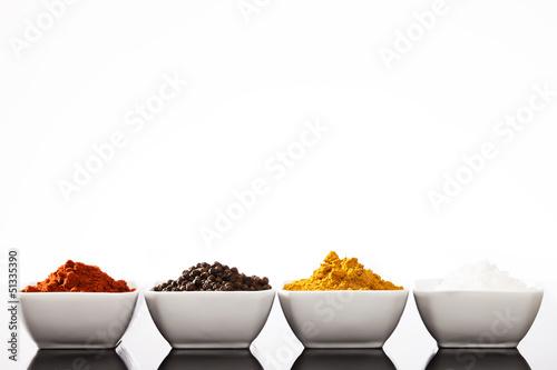reihe kleiner schälchen mit paprika pfeffer curry und salz