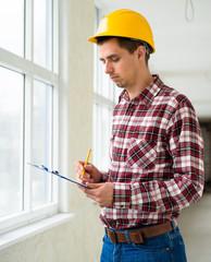 Elegant engineer writing on notepad