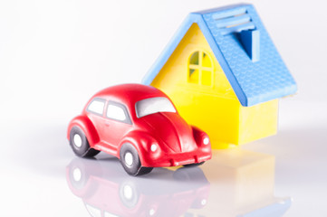 small red toy beetle car and house on white