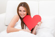 Young Beautiful Woman Lying On Bed And Holding Heart Shape