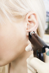 girl pierced ear with a special equipment.