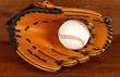 Baseball glove and ball on wooden background