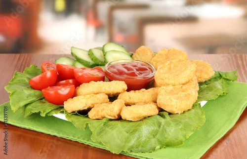 Fried chicken nuggets with vegetables and sauce on table in