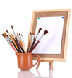 Small easel with sheet of paper and art supplies isolated