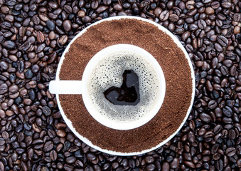 Background of coffee grains and a cup of coffee