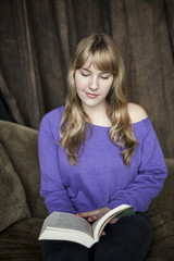 Young Woman with Beautiful Blue Eyes Reading a Book