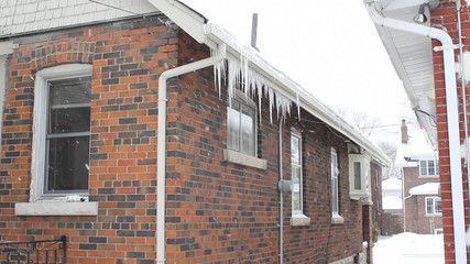 Snow falls and icicles hang from a suburban house. Toronto.