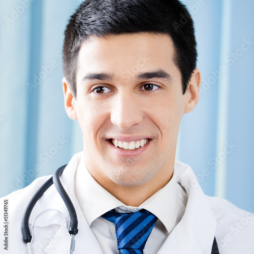 Happy smiling young doctor at office
