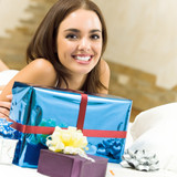 Happy smiling woman with gifts at home