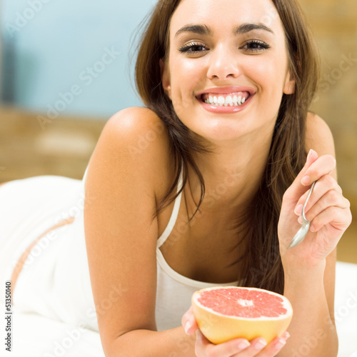 Portarit of young woman eating grapefruit at home