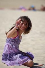 fillette sur la plage en robe mauve