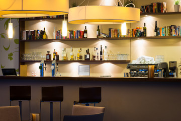 hotel lounge bar with bottle shelfs and seats, tables, ligh