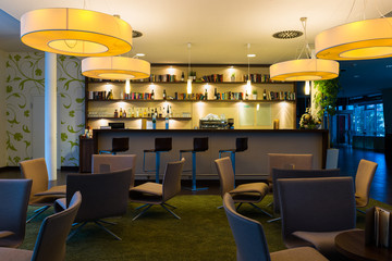 hotel lounge bar with bottle shelfs and seats, tables, lights