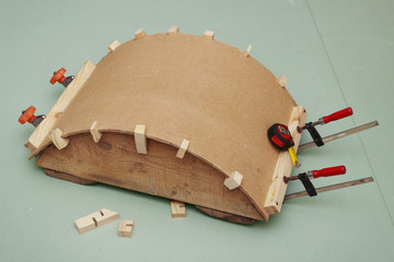 Gluing the arch of hardboard  on  rule