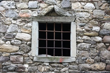 window with a metal grid on an old stone barn