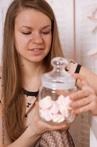 Young woman gobbling up marshmallows with a smile