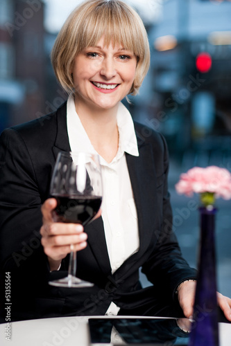 Happy businesswoman holding wine glass