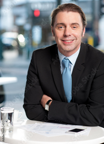 Smiling businessman at cafe
