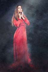 Fairy woman in red dress in smoke and fire