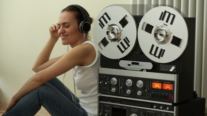 Girl in headphones listening to music from retro tape recorder