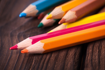 Close up of color pencils isolated on brown background