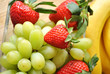 Grapes and Strawberries in Front of Yellow Bananas