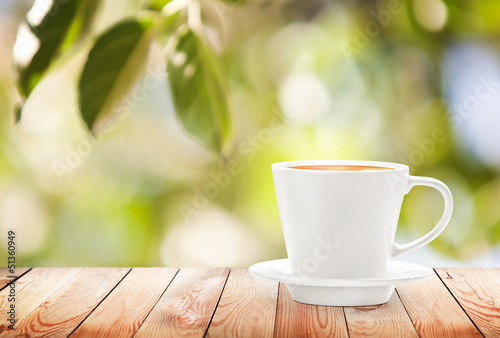 Cup of hot drink on summer background, free space for text