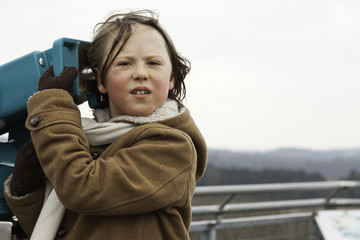 Playful funny young boy with long hair holding telescope.