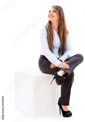 Businesswoman sitting on a cube.