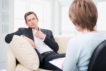 Oppressed man talking with psychologist