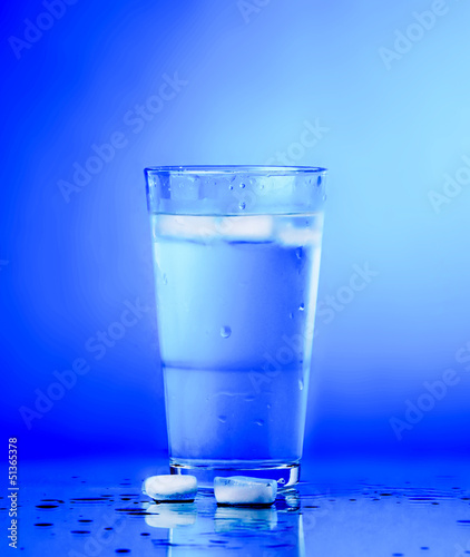 Leinwandbild Motiv Glass of water on blue background. water with ice in glass