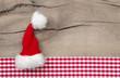 Weihnachtskarte mit einer roten Zipfelmütze auf Holz kariert