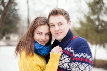 portrait of a young happy couple in colored sweaters