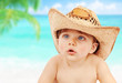 Baby boy in cowboy hat on beach