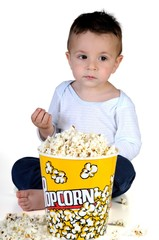 Little boy eating popcorn, isolated