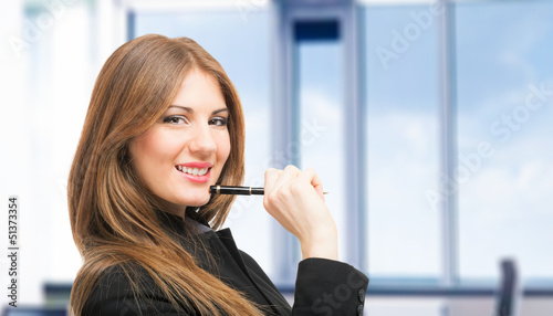 Smiling woman holding a pen
