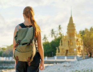 Young woman looking at golden pagoda. Hiking at Asia